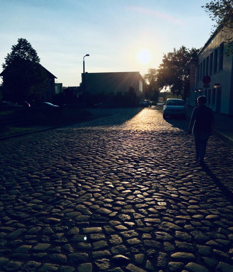 Streetphoto mit Kopfsteinpflaster und einsamer Person, die Richtung Sonne geht